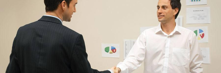 Two people shaking hands with charts on the wall in the backgorund