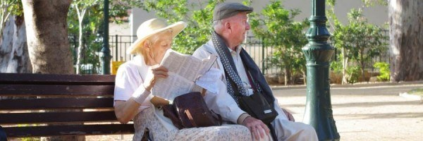 A retired couple relaxing on a park bench.