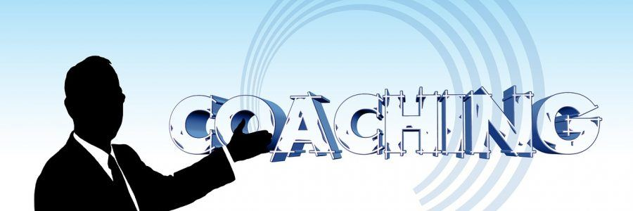 "Illustration of a man pointing to the word ""coaching"""