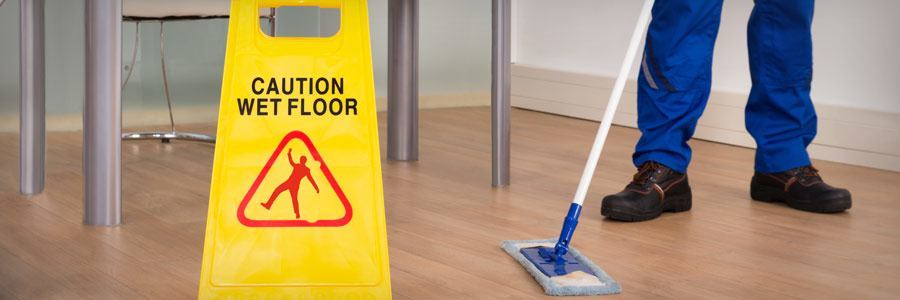 "Sign saying ""Caution: wet floor"" with person mopping in background"