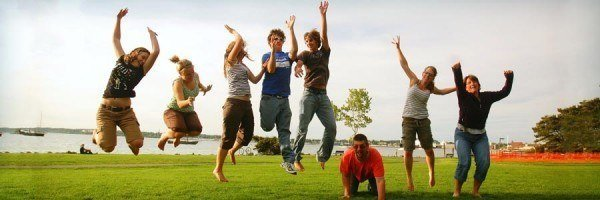 A group of people jumping in the air on a grassy area in front of a lake.