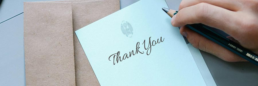 A person writing a thank-you card.