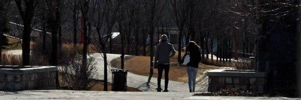 Couple walking through a park in Winnipeg, Manitoba