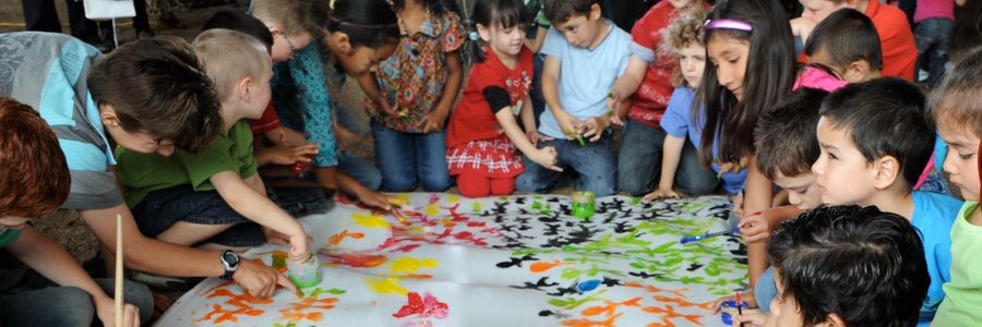 Children from a variety of backgrounds working on a multi-colored diversity mural together
