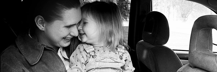 Mother and daughter cuddling and laughing in a car