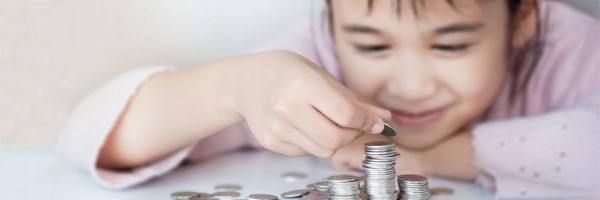 A young girl stacking piles of quarters.