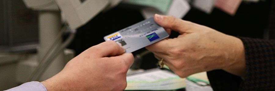 One person handing a credit card to another person