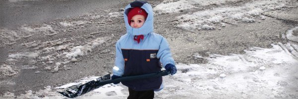 A young child dressed for a Manitoba winter, holding a snow shovel