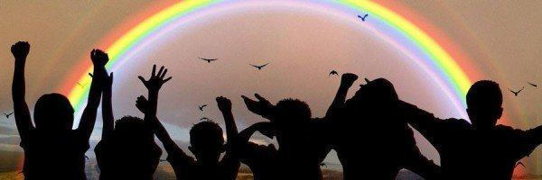 Silhouettes of children waving their hands in the air in front of a rainbow