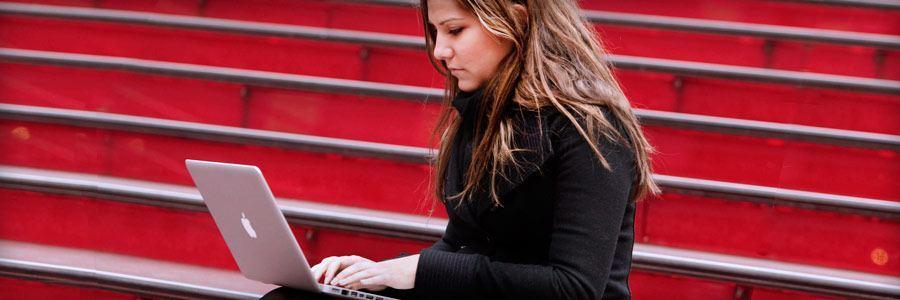 Woman working outdoors on a laptop.