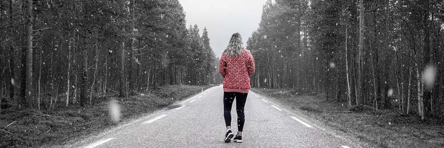 woman walking as snow falls