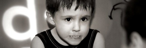 Worried-looking child biting his lip.