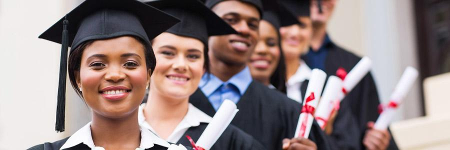 Graduates of post secondary education wearing caps and gowns and holding diplomas.