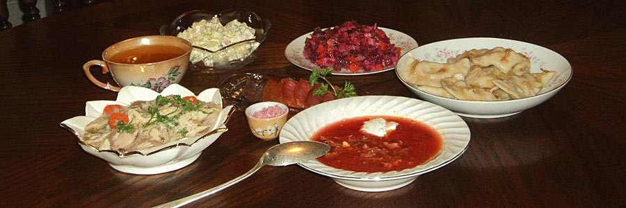 Ukrainian food. Clockwise: Borsch(plate with spoon), Kholodets, Kompot, Olivye, Vinigret, Varenyky. Center: Cured Salmon, Horseradish.