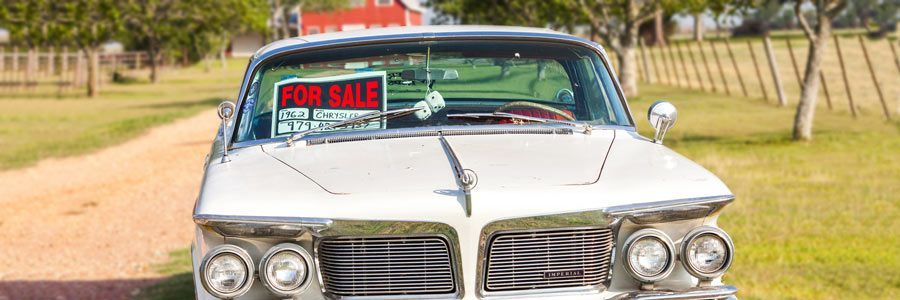 A vintage car on the roadside with a for sale sign in the window.