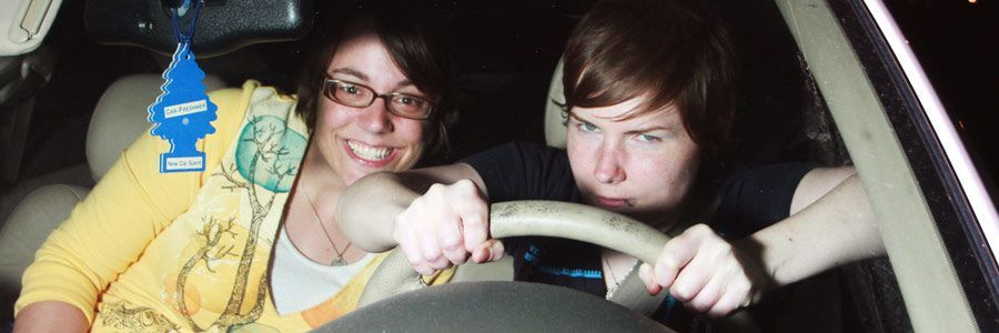Two women having fun during a driving lesson.