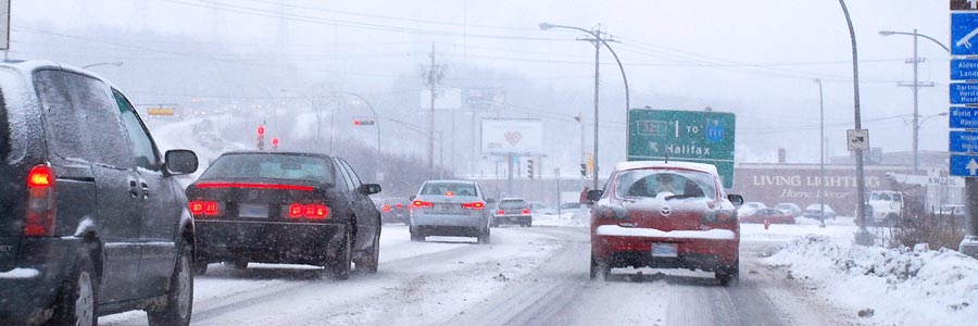 Cars driving in a city on a snowy day in Canada.