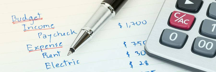 A pen, a calculator, and some household budget numbers written on a paper.