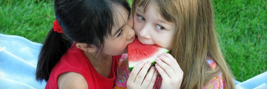 Two children sharing a piece of watermelon.