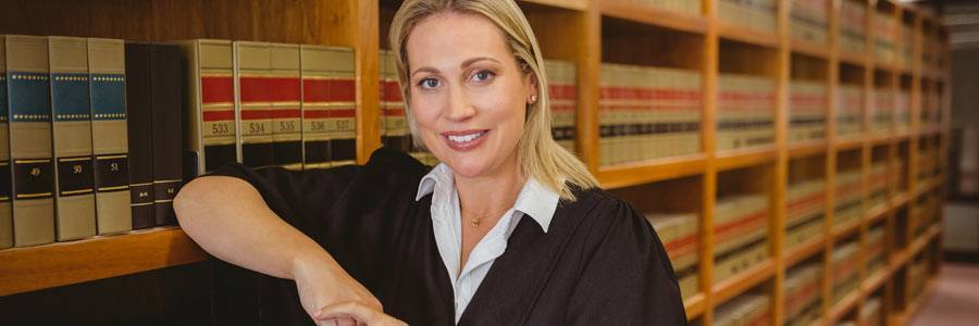 Smiling lawyer leaning on shelf in law library