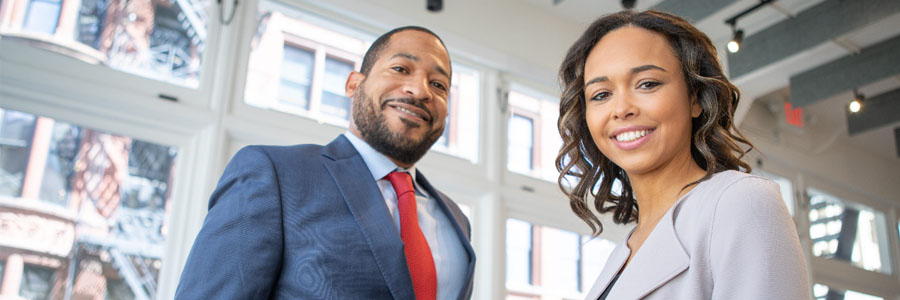 Man and woman wearing business suits smiling at camera