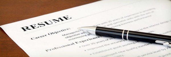 A resume and pen lying on a desk.