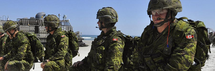 Canadian soldiers set a perimeter position after disembarking a U.S. Navy landing craft during a training exercise.