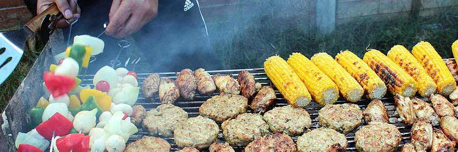 Vegetable skewers, corn on the cob, and meats on a barbeque.