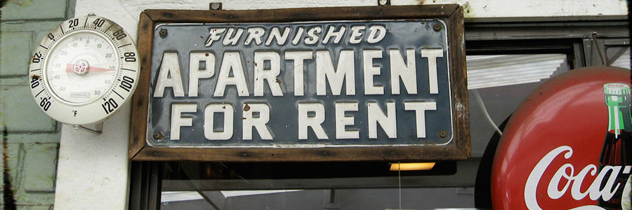 "A vintage sign reading ""Unfurnished Apartment for Rent""."