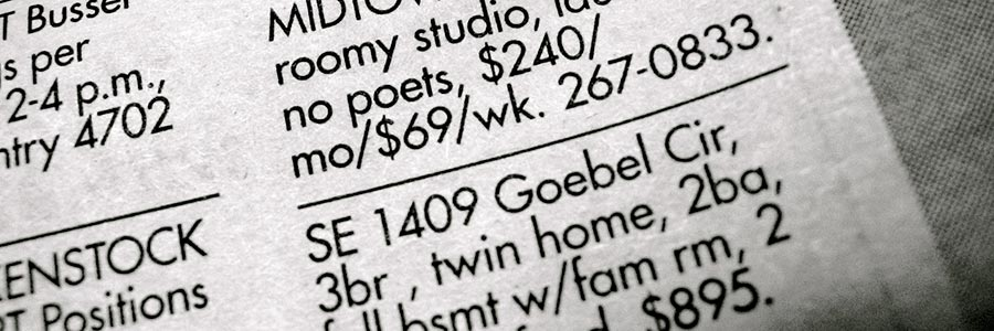 A close-up of apartment classified ads in a newspaper.