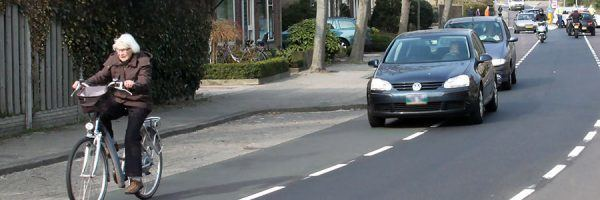 Cycle lanes in Oudorp, with cars passing a cyclist.