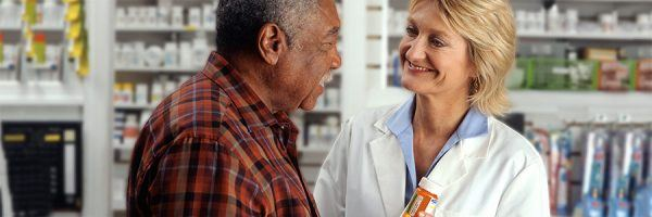 An older African-American man talks to a Caucasian female pharmacist as she explains his prescription.