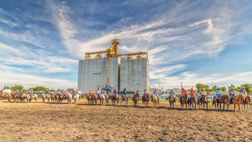 Grain elevator behind a row of horseback riders in the Cartwright, Killarney and Boissevain area.