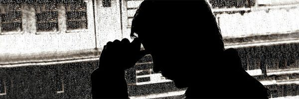 A silhouette of a man holding his head in his hands.