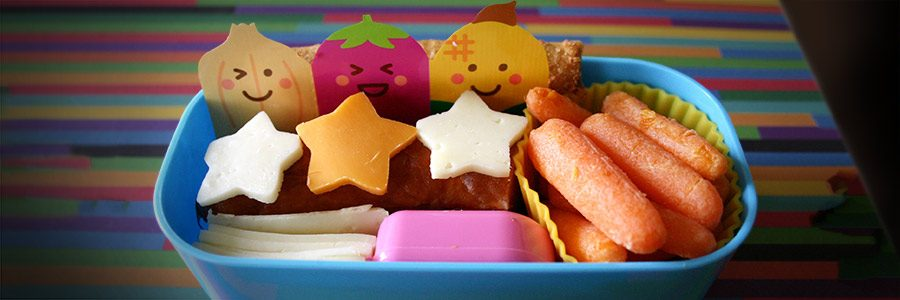 A school lunch packed in a lunch box with some construction paper characters.