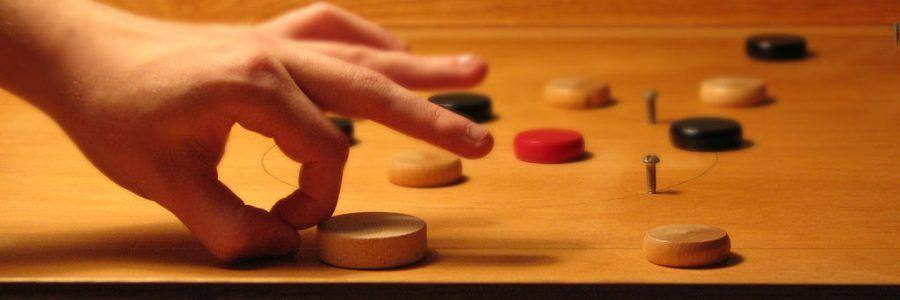 fingers flicking a shooter on a pitchnut board game