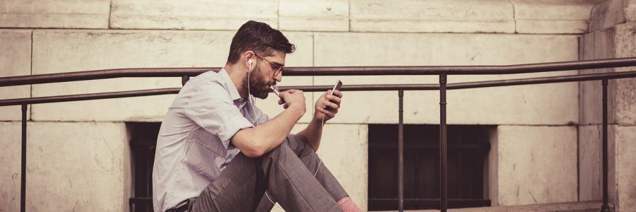 Man with headphones looking at his mobile phone