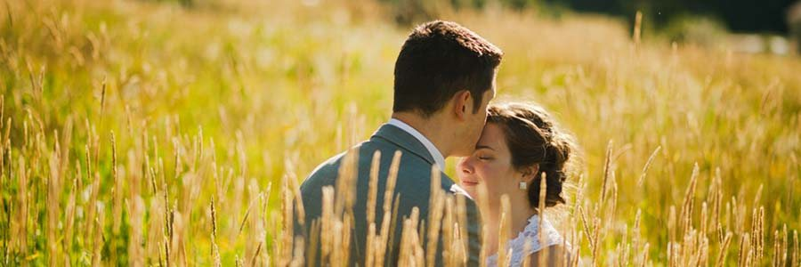 groom kissing bride on forehead amid tall prairie grass