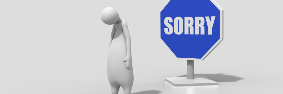 "creature with head hung low with ""sorry"" sign"