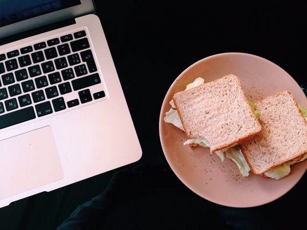 laptop with a sandwich plate near it
