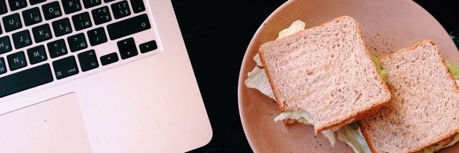laptop with a sandwich plate near it