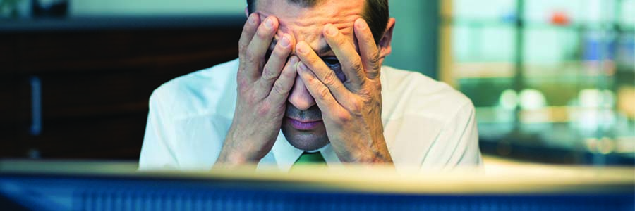 Man with hands on face, facing a computer screen feeling frustrated