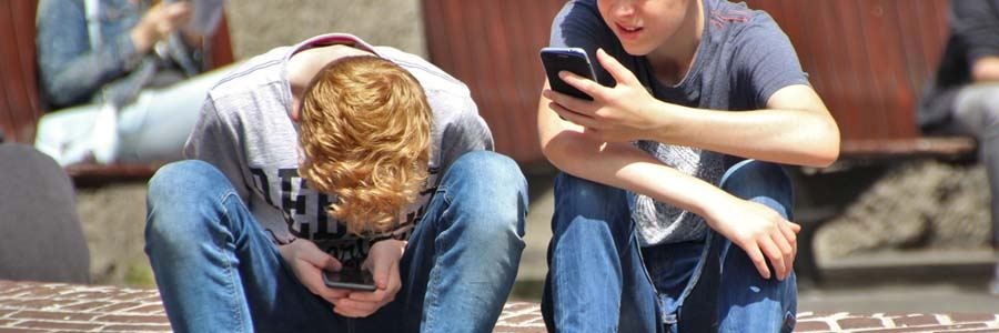 two boys on their mobile phones