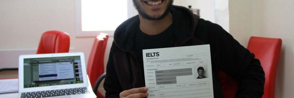 Man smiling and showing IELTS scores