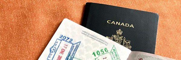 Open passport on top of Canadian passport