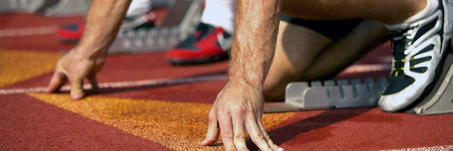 close-up of a runner's arms and legs at the starting mark