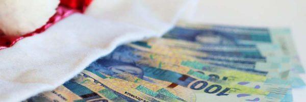 Money in bills fanned out near a Santa hat