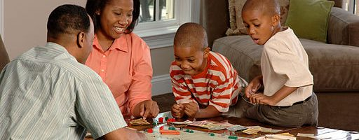 Family of four playing a board game