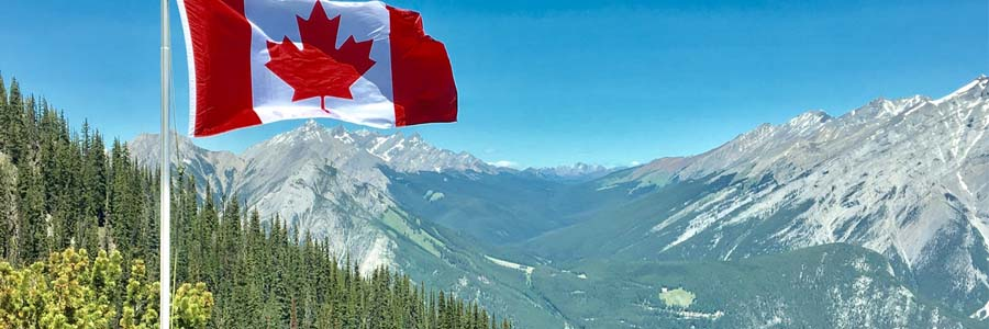 Canadian flag atop a mountain range