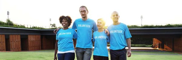 A group of four diverse volunteers arm-in-arm